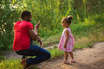 Black African father takes photo of his daughter