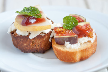 Bruschetta with goat cheese, pear and figs on white plate