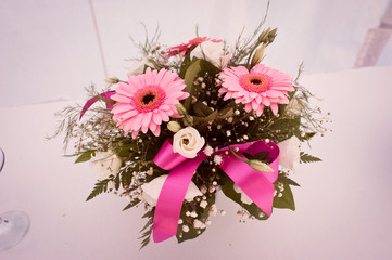 A bouquet of pink daisies and greenery, tied with a pink ribbon
