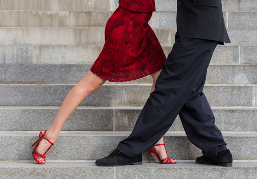 man and woman dancing tango on street staircase