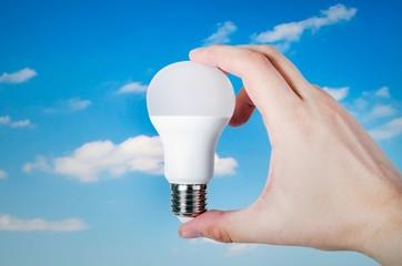 Hand holding LED bulb on sky background