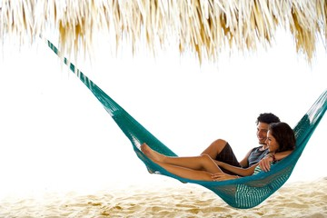 This young couple relax In a hammock on vacation, under a palapa, cabana on the beach in central america