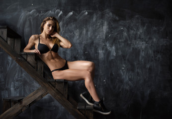 Beautiful young athletic girl in underwear on dark background