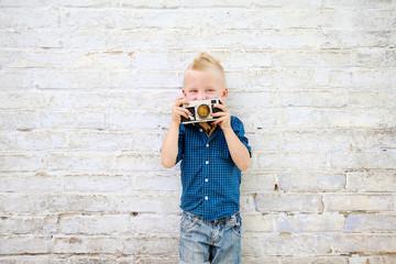 мальчик с фотоаппаратом фотографирует возле белой кирпичной стены