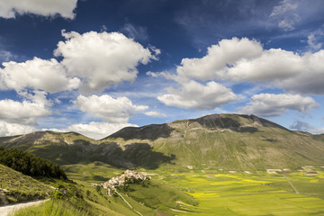 Famous mountain village of Castelluccio di Norcia with beautiful summer landscape at Piano Grande (Great Plain) mountain plateau in the Apennine Mountains on a sunny day, Umbria, Italy