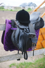 The horse riding equipment with a black helmet outdoors