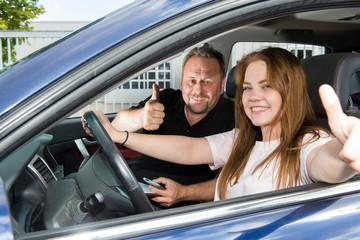 Fahrlehrer und Fahrschülerin im Auto