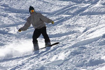 Close Up on a Snowboarder Carving Turns With His Board in the Snow