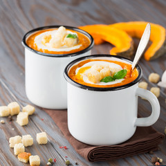 Homemade pumpkin soup with cream, croutons and basil in enamel mugs on rustic wooden background, selective focus