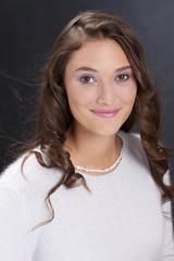 Hübsche junge Frau mit hellem Pullover im Studio