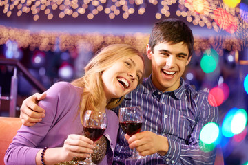 Young couple with wineglasses laughing