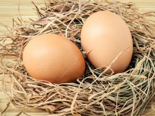 Closeup brown chicken eggs in a straw nest . Fresh organic eggs