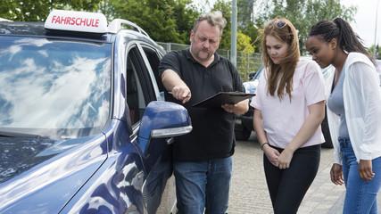 Fahrlehrer erklärt Fahrschülerin den Seitenspiegel