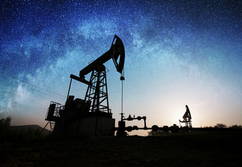 Silhouette of two oil pumps are working on the oil field in the evening under night sky with stars. Oil industry equipment. Milky way shines above