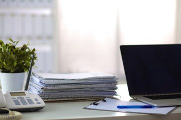 stack of papers on the desk with computer