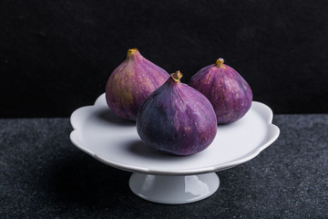 Fresh figs on white plate on dark background