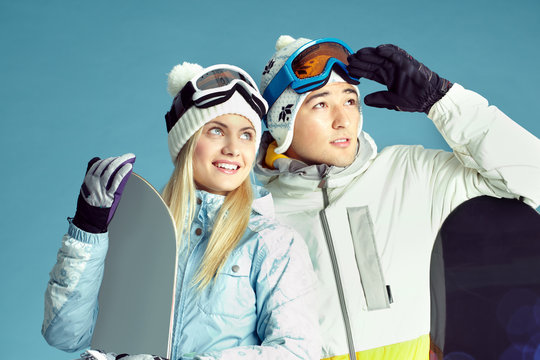 Two loving couple of snowboarders looking at something