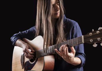 beautiful young woman playing acoustic guitar