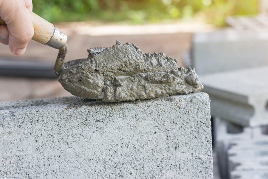 Cement or mortar, Cement mix with a trowel in a hand on the brick for construction work.