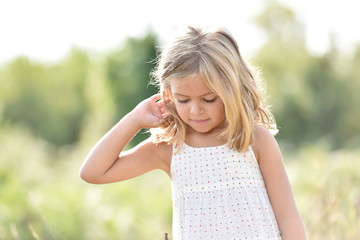 Portrait of cute little blond girl in countryside, summertime