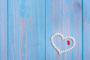 Red candy heart laying on white painted rustic wooden background
