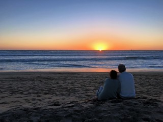 Romantic couple watches a golden sunset