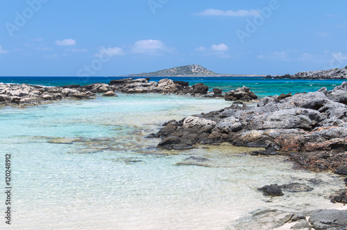 Wall mural Rocky wild beach with azure clear color water