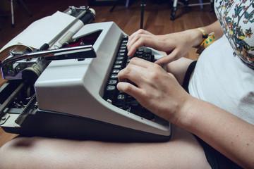 Mujer joven escribiendo en una máquina de escribir antigua