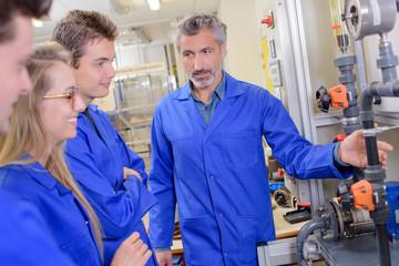 Teacher explaining machinery to apprentices