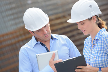 Man and woman in hardhats looking at clipboard