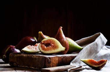 Cut purple figs on the board. Vintage wooden background, low key