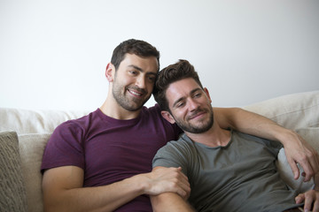 Gay Male Couple On Sofa At Home Watching TV