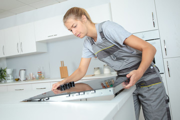 Woman fitting ceramic hob into kitchen