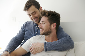 Gay Male Couple At Home Relaxing In Bed Together