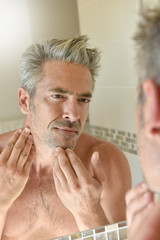 Mature man in bathroom checking beard