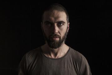 portrait of a handsome bearded man on dark background