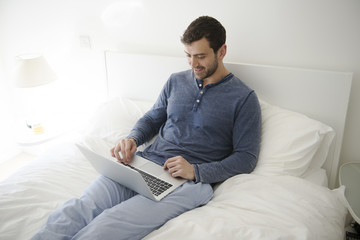 Man Relaxing In Bed At Home Looking At Laptop Computer