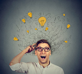Happy man in glasses looking up with light idea bulb above head