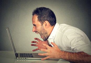 Angry furious business man screaming at computer