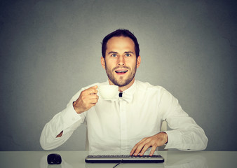 Amazed man using computer holding cup of coffee.