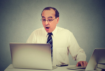 shocked man sitting in front of laptop computer