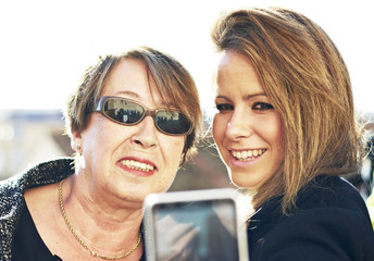 Mother and daughter becoming a selfie with a smartphone