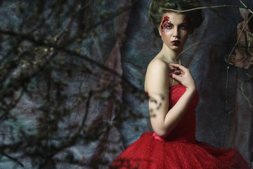 Woman in red dress. Fantastic Hairstyle and make up. Wall mural