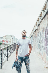 Knee figure of young beautiful caucasian bearded tattooed man outdoor in the city, with hand in pocket holding jeans jacket, overlooking pensive - serious, fashion, thinking future concept