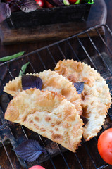 Caucasian cuisine - Cheburek pie with meat on a wooden background with vegetables