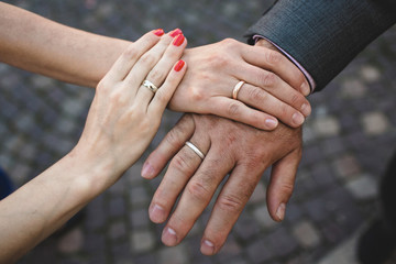two female hands on the man's hand
