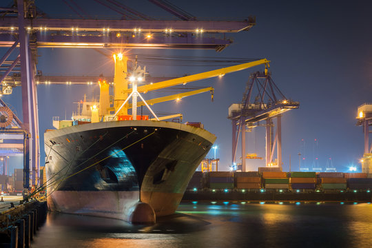 Container Cargo freight ship with working crane bridge in shipyard at dusk for Logistic Import Export background..