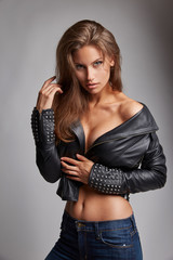 Beautiful sexy woman with amazing hair and magnificent eyes in leather black jacket and blue jeans posing in studio