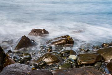 Mystischer Steinstrand mit Wellen auf Skye, Schottland, Langzeitbelichtung