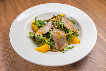 salad with baked duck on white plate